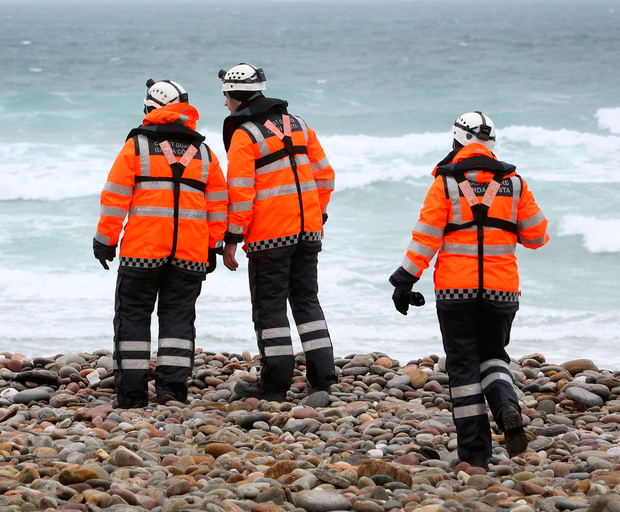 Members of the Irish Coast Guard searching the coast near Belmullet, Co Mayo, for the missing crew of Rescue 116 Photo: Frank McGrath