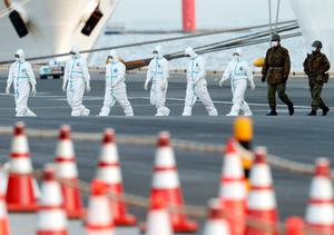 Fears: Workers and army officers wearing protective suits walk away from the cruise ship Diamond Princess in Yokohama,  Japan, yesterday. Photo: Reuters