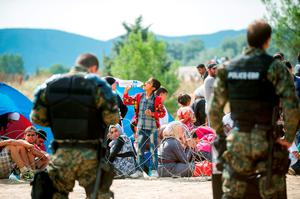 Migrants wait to cross the Macedonian-Greek border near the town of Gevgelija on August 21, 2015. At least five migrants were slightly hurt August 21 when Macedonian police threw noise grenades to drive back refugees from the country's border with Greece, an AFP photographer at the scene said. More than 3,000 mostly Syrian refugees are stuck in no-man's land near the Greek village of Eidomeni after Macedonia August 20 declared a state of emergency and sent troops to help stem the flow of migrants attempting to cross the Balkan country to reach northern Europe. AFP PHOTO / ROBERT ATANASOVSKIROBERT ATANASOVSKI/AFP/Getty Images