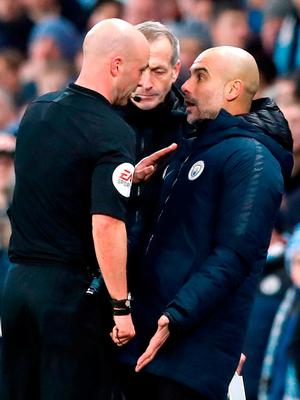 Manchester City manager Pep Guardiola (right) is spoken to by referee Anthony Taylor. Photo: PA