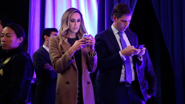 Eric Trump (R) and his wife Lara Yunaska use their iPhones during a campaign rally in the Lakawanna College Student Union November 7, 2016 in Scranton, Pennsylvania.