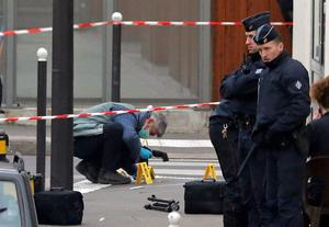 French investigating police officer takes photos outside the door of the French satirical newspaper Charlie Hebdo's office. (AP Photo/Francois Mori)