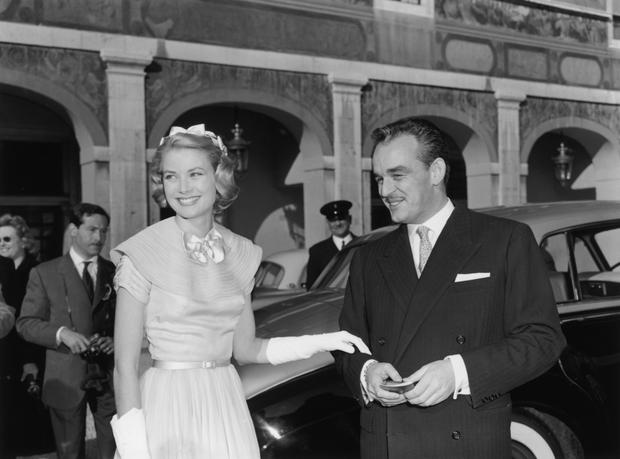 Prince Rainier of Monaco and Princess Grace (1929 - 1982) greet well-wishers in the palace courtyard in Monte Carlo prior to their wedding, 18th April 1956. (Photo by Reg Birkett/Keystone/Hulton Archive/Getty Images)
