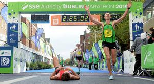 Eoin Flynn, Ireland, right, celebrates crossing the line as Thomas Cornthwaite, from Lanchashire, England, catches his breath after the SSE Airtricity Dublin Marathon 2014. Merrion Square, Dublin. Photo: Pat Murphy/SPORTSFILE
