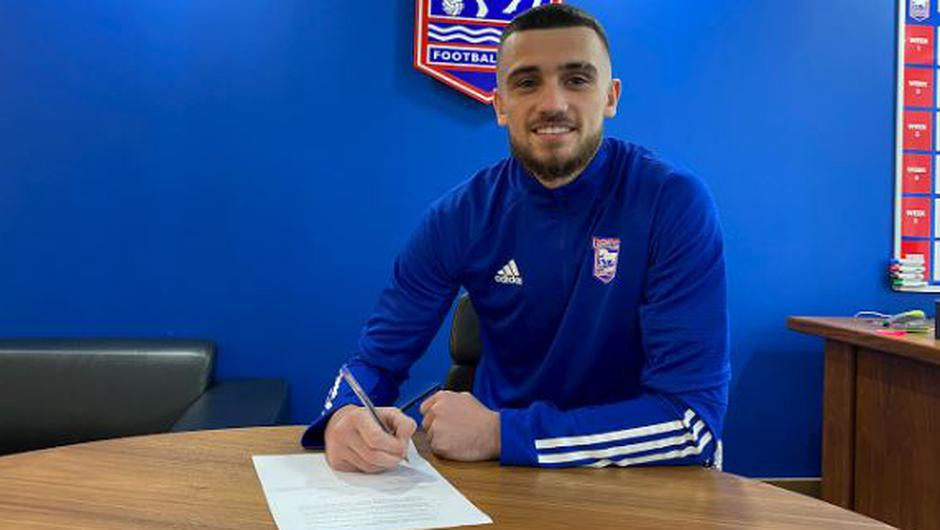 Troy Parrott pictured signing for Ipswich on loan for the remainder of the season. Image credit: Ipswich Town.