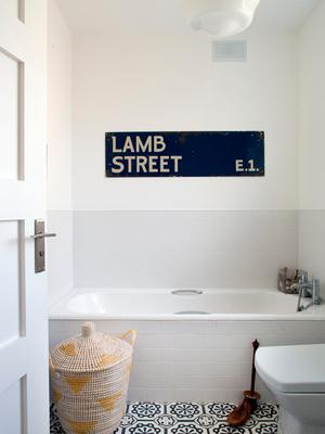 The bathroom still has the original 1950s bath, while the Lamb Street sign is from Joy Thorpe Antiques