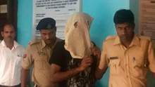 Vikat Bhagat is led into court by police in Goa