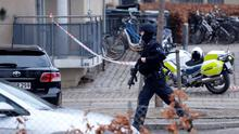 """An armed security officer runs down a street near a venue after shots were fired where an event titled  """"Art, blasphemy and the freedom of expression"""" was being held in Copenhagen, Saturday, Feb. 14, 2015. Danish media say several shots have been fired at a cafe in Copenhagen where a meeting about freedom of speech was being held, organized by Swedish artist Lars Vilks, who has faced numerous threats for caricaturing the Prophet Muhammad in 2007. (AP Photo/Polfoto, Kenneth Meyer) DENMARK OUT"""