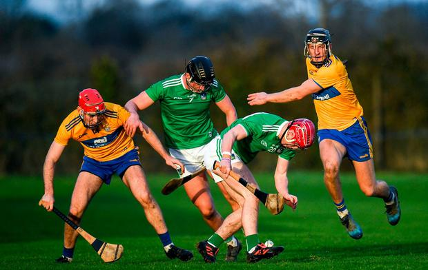 Josh Considine and Paddy O'Loughlin of Limerick scramble for possession against Niall Deasy and Shane Golden of Clare. Photo: Harry Murphy/Sportsfile