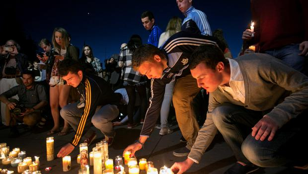 People place candles in front of a memorial during a candlelight vigil for the victims of the Berkeley balcony collapse in Berkeley, California June 17, 2015. Three men and three women in their early 20s, including an American friend of the Irish students, died in the collapse, and seven others were hospitalized. REUTERS/Elijah Nouvelage