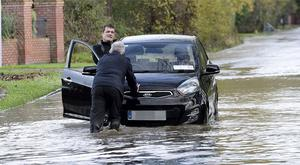 Man  helping driver push his car that cut out as he attempted to drive through flooded road under railway bridge near Bettystown, Co. Meath. Picture: Caroline Quinn