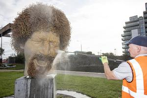 A man cleans the statue of Luke Kelly on the corner of Guild Street and Sheriff Street after it was vandalised again Pic: Mark Condren