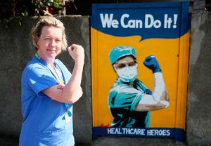 Yes we can: Healthcare assistant Michelle Farrell poses beside a mural by Irish artist Emmalene Blake on a gate in south Dublin thanking healthcare workers. Photo: Brian Lawless/PA Wire