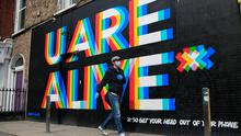 Sign of the times: A poster in Dublin city centre by Dublin artists Maser and Aches reminds passers-by that life still goes on amid the crisis