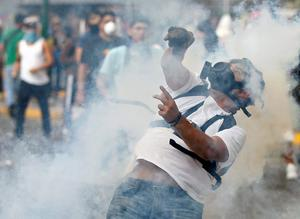 A demonstrator returns a tear gas grenada towards police during a protest against the government of President Nicolas Maduro in Caracas