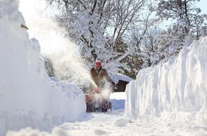Paul Lorenzo clears snow along Powers Road in Orchard Park, N.Y. (AP Photo/The Buffalo News, Harry Scull Jr.)