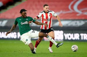 Plymouth Argyle's Jerome Opoku and Sheffield United's Billy Sharp battle for the ball. Photo: PA