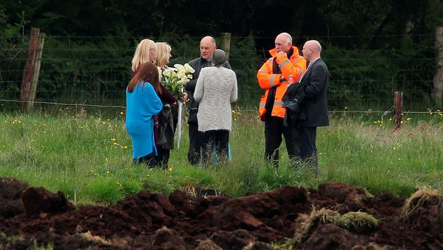 Local priest Father John O'Brien and Geoff Knupfer (wearing orange jacket), head of the investigation team for the Independent Commission for the Location of Victims' Remains (ICLVR), with members of Seamus Wright's family at the site in Coghalstown, Co Meath, where two bodies were discovered on a reclaimed bog where three of the IRA Disappeared are believed to be secretly buried