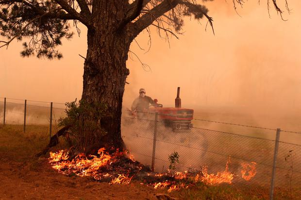A farmer drives a tractor as he uses a hose to put out a fire burning in his paddock and near homes on the outskirts of the town of Bilpin on December 19, 2019 in Sydney, Australia. (Photo by David Gray/Getty Images)