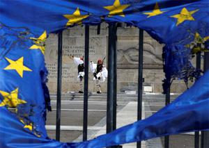 Presidential guards are framed through a burned EU flag in front of the Tomb of the Unknown Soldier by the parliament in central Syntagma square in Athens