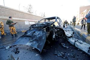 Policemen look at the wreckage of a car at the scene of a car bomb outside the police college in Sanaa, Yemen