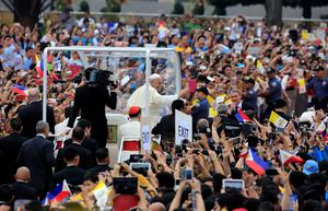 Pope Francis waves to pilgrims as he passes by with his motorcade during a meeting with youths at the University of  Santo Tomas (UST) in Manila January 18, 2015. REUTERS/Romeo Ranoco