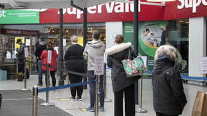 Keeping a distance: Shoppers follow floor signs to aid social distancing outside a SuperValu in Lucan yesterday. Photo: Collins
