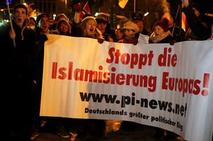 People take part in a march of a grass-roots anti-Muslim movement in Cologne January 5, 2015. The rise of the group, Patriotic Europeans Against the Islamisation of the West (PEGIDA), has shaken Germany's political establishment. The text reads 'Stop the islamisation of Europe!'        REUTERS/Wolfgang Rattay