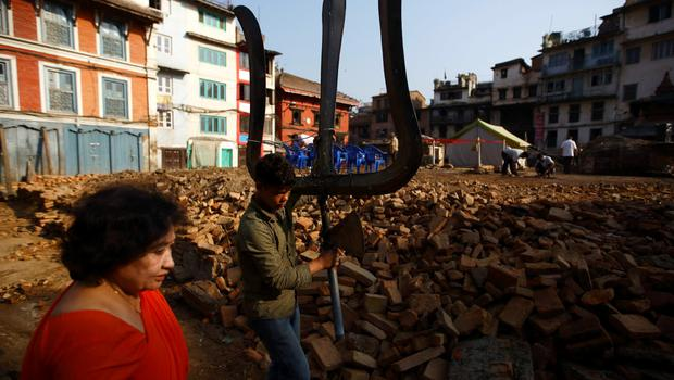 "A boy walks along the debris of a collapsed temple carrying a trident, which is locally called ""Trishul"", a weapon used by Lord Shiva also known as the god of destruction, after the April 25 earthquake in Kathmandu, Nepal June 8, 2015. REUTERS/Navesh Chitrakar"