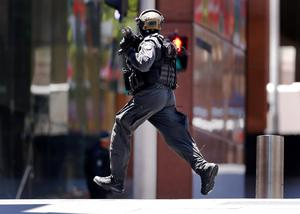 A police officer runs across Martin Place near Lindt cafe, where hostages are being held. Photo: Reuters/David Gray.