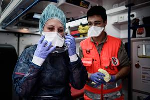 Red Cross volunteers get ready prior to an intervening in the home of a woman with symptoms of Covid-19 (Photo by PHILIPPE LOPEZ/AFP via Getty Images)