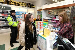 Support: Community volunteer Amy Deacon collects a prescription with Garda Sgt Paul Kealy from pharmacist Pauline McAlea at McCartan's pharmacy in Maynooth, Co Kildare. Photo: Mark Condren