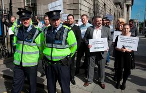 Members of the Gardai beside Greyhound non-striking workers who face losing their job as a result of the 13-week strike protesting against the strikers outside the high court, Dublin. Photo: Gareth Chaney Collins