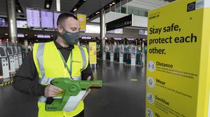 Clean-up: A staff member disinfects Terminal 2 in Dublin Airport yesterday, using an electrostatic gun. Photo: Colin Keegan, Collins Dublin
