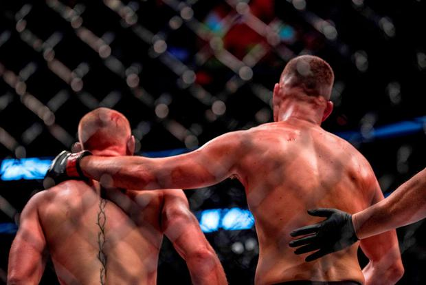 Nate Diaz (red gloves) reacts with Conor McGregor (blue gloves) during UFC 202 at T-Mobile Arena