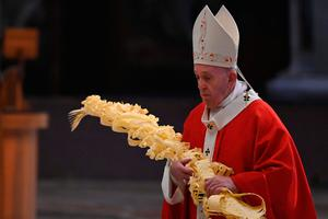 Pensive: Pope Francis holds a palm branch as he celebrates Palm Sunday behind closed doors in St Peter's Basilica in Rome. Photo: ALBERTO PIZZOLI/POOL/AFP via Getty Images