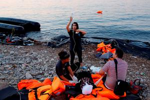 Volunteers provide medical help to a pregnant Syrian refugee woman shortly after she arrive on a overcrowded dinghy at a beach on the Greek island of Lesbos after crossing a part of the Aegean Sea from the Turkish coast, September 19, 2015.REUTERS/Yannis Behrakis