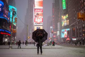 A man stands under an umbrella while photographing a snow storm in Times Square, New York, January 26, 2015.  REUTERS/Adrees Latif