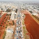 An aerial photo shows displaced Syrians driving through Hazano in the northern countryside of Idlib, after fleeing towards areas further north near the border with Turkey. Photo: Omar HAJ KADOUR / AFP