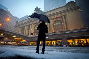 A man tries to hail a taxi in front of Grand Central Terminal as it snows in the Manhattan borough of New York January 26, 2015.  REUTERS/Carlo Allegri