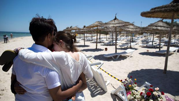 DISTRAUGHT: Holiday-makers hug each other as they visit the scene on the beach where Irish nurse Lorna Carty was shot dead along with 37 others by a crazed ISIL gunman