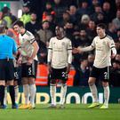 Referee Craig Pawson is surrounded by Manchester United players after Liverpool's Roberto Firmino (not pictured) scores, a goal that was eventually ruled out