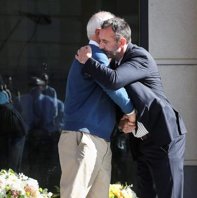 Berkeley Mayor Tom Bates (L) hugs Philip Grant, Consul General of Ireland to the Western United States, following a wreath-laying ceremony at the scene of a 4th-story apartment building balcony collapse in Berkeley