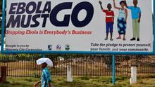 """(FILES)-- A file photo taken on February 23, 2015 shows a man walking past an ebola campaign banner with the new slogan """"Ebola Must GO"""" in Monrovia. The World Health Organization on May 9, 2015 declared Liberia to be free of the Ebola virus, which has killed more than 4,700 people in the west African country. AFP PHOTO / ZOOM DOSSOZOOM DOSSO/AFP/Getty Images"""