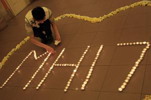 A man lights candles before a special prayer for the victims of the crashed Malaysia Airlines Flight 17, in Kuala Lumpur, Malaysia, Tuesday, July 22, 2014.  (AP Photo/Lai Seng Sin)