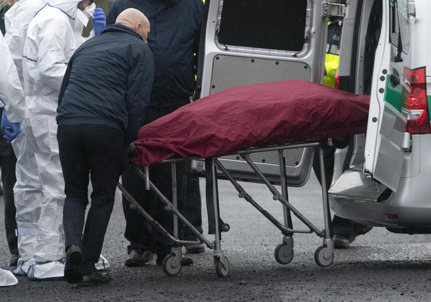 Horror: Gardaí remove the boy's remains in                   Coolock, Dublin. Photo: Colin Keegan/Collins