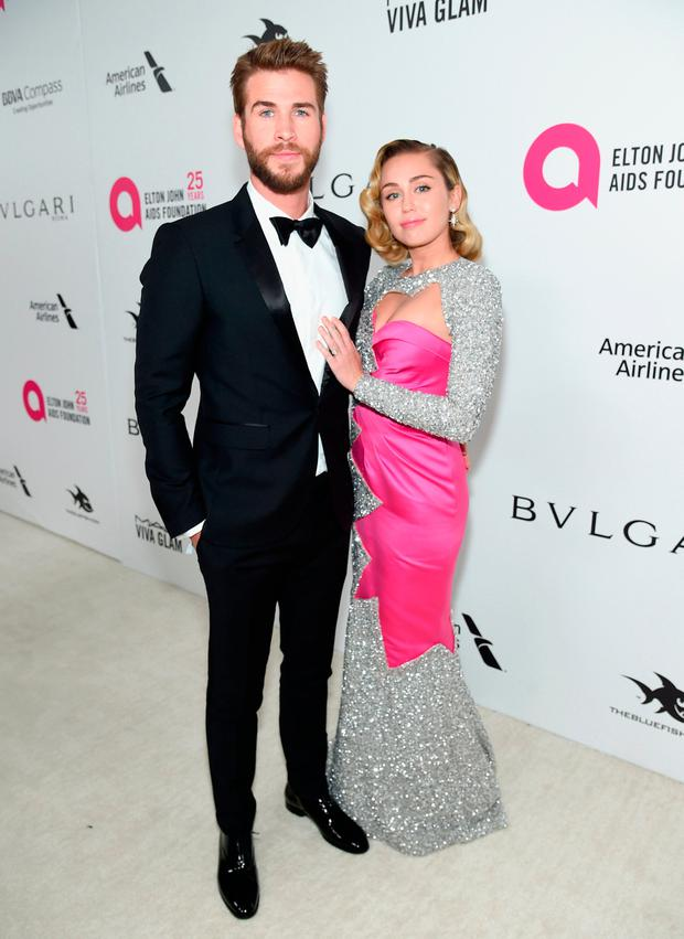 Liam Hemsworth (L) and Miley Cyrus attend the 26th annual Elton John AIDS Foundation Academy Awards Viewing Party sponsored by Bulgari, celebrating EJAF and the 90th Academy Awards at The City of West Hollywood Park on March 4, 2018 in West Hollywood, California. (Photo by Jamie McCarthy/Getty Images for EJAF)