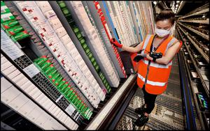 A staff member sorts through packs among hundreds of rows of medicines. Picture: Steve Humphreys