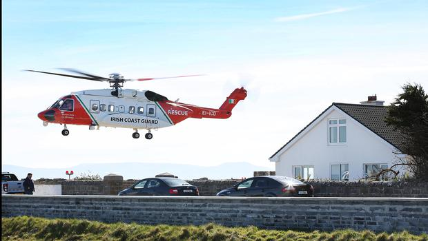 An Irish Coast GuardHelicopter lifts off from Blacksod Pier next door to the house where family members of the missing crew are watching from as the search continues for Rescue 116 along Blacksod coastline in Co Mayo. Pic Steve Humphreys 25th March 2017