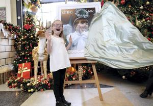 SUPRISE: Schoolgirl  Paris Curtis (7) is delighted as the picture of her as an angel at the Mansion House Crib is unveiled as An Post's new Christmas stamp